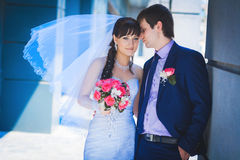 Newlyweds against a blue modern building Royalty Free Stock Images