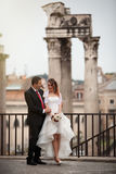 Newlyweds in the ancient city. Happy married couple. Rome, Italy. A smiling groom embracing his bride in white wedding dress. They are located in the historic Stock Image