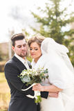 Newlyweds in autumn park, the groom embracing his bride. Stock Images