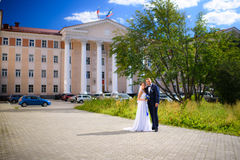Newlyweds in the background of an building. Happy young Newlyweds in sunny summer day Stock Images