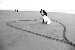 Newlyweds on beach. Couple kissing on beach standing inside of heart carved in sand Stock Photography