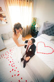 Newlyweds in bedroom with heart. Love, tenderness, caresses. Just married. First night. On the bed rose petals heart-shaped Royalty Free Stock Images