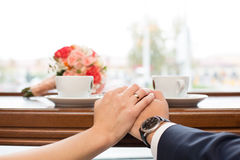 Newlyweds behind show-window in cafe and  cup of coffee Stock Photography