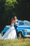 Newlyweds at Blue Cabriolet. Newlyweds hugging at blue cabriolet Royalty Free Stock Photo