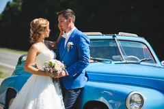Newlyweds at Blue Car. Newlyweds with wedding bouquet at blue car Stock Photo