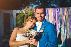 Newlyweds with Bouquet. Smiling newlyweds holding wedding bouquet Royalty Free Stock Image