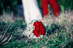 Newlyweds. Bridal bouquet and blurred newlyweds Stock Photos