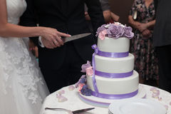 Newlyweds carving delicious white wedding cake with purple roses Royalty Free Stock Photography