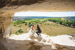 Newlyweds in Cave. Newlyweds sitting at table in cave at sunny day Stock Photo