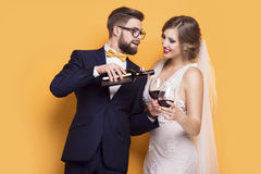 Newlyweds celebrating drinking red wine. Standing on a yellow background Stock Image