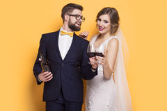 Newlyweds celebrating drinking red wine. Standing on a yellow background Royalty Free Stock Photos