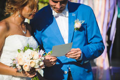 Newlyweds with Certificate. Bride and groom looking at wedding certificate Stock Images