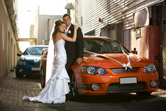 Newlyweds che abbracciano in un vicolo con le automobili di cerimonia nuziale Immagini Stock Libere da Diritti