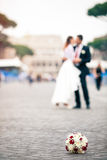 Newlyweds in the city. Bouquet of flowers on the ground on cobblestones. Colosseum. Rome Italy. Royalty Free Stock Photos