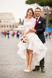 Newlyweds in the city. Happy married couple. A smiling groom embracing his bride in white wedding dress. They are located in the historic center of Rome, Italy Stock Images