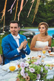 Newlyweds Clapping Hands. At festive table Royalty Free Stock Photo