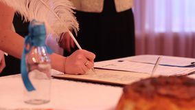Newlyweds confirming creation of new family by signing marriage certificate. Stock footage stock video