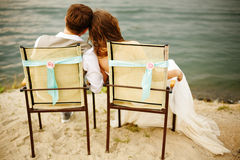 Newlyweds couple sitting near water on the beach Royalty Free Stock Images