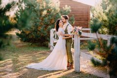Newlyweds in cowboy style standing and hugging on ranch. Summer day stock photos