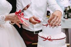 Newlyweds cut wedding cake stock image