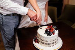 Newlyweds cut the wedding cake decorated with fresh fruits. Bride and groom cut  wedding cake Stock Images