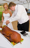 Newlyweds cutting whole pig Stock Photography