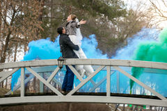 Newlyweds dancing on bridge covered with blue smoke Royalty Free Stock Photography