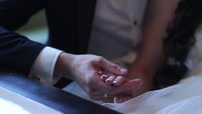 newlyweds de mens houdt de meisjes` s hand mannelijke en vrouwelijke handen dichtbij een boeket en een kaars stock videobeelden