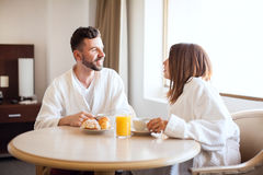 Newlyweds eating breakfast in a room Stock Images