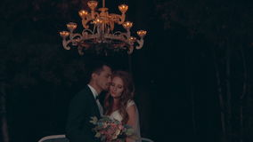 Newlyweds embrace at night, standing under chandelier with lights in dark forest stock video