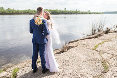 Newlyweds embraces outdoors. Royalty Free Stock Photography