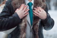 Newlyweds embraces outdoors in the winter. The bride groom holding hands Royalty Free Stock Photo