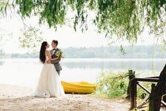 Newlyweds embracing near the boat. Beautiful newlyweds embracing near the yellow boat on the sunny river bank Stock Photo