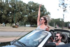 Newlyweds enjoying a trip in a convertible. stock images