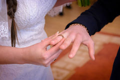 Newlyweds exchange rings. Groom puts the ring on the bride`s hand in marriage registry office Royalty Free Stock Photography