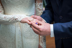 Newlyweds exchange rings. Groom puts the ring on the bride`s hand in marriage registry office Stock Image