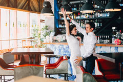 Newlyweds expressively dancing in the bar. Hipster wedding couple. Newlyweds expressively dancing in the bar Royalty Free Stock Photography