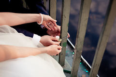 Newlyweds fix the lock on the bridge Stock Images