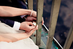 Newlyweds fix the lock on the bridge Royalty Free Stock Photos