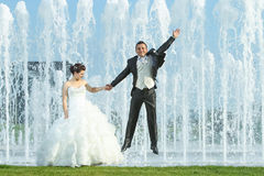 Newlyweds in front of water fountain Stock Image