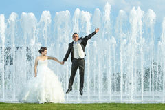Newlyweds in front of water spray fountain Stock Photos
