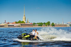 Newlyweds go on jet skis, the bride and groom on the background Royalty Free Stock Photography