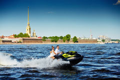 Newlyweds go on jet skis, the bride and groom on the background. Of Peter and Paul Fortress, the water area of the Neva river, boat, beach, blue sky, clear Stock Image