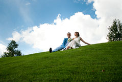 Newlyweds on a green lawn of background the sky Stock Photos