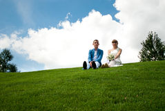 Newlyweds on a green lawn of background the sky Royalty Free Stock Photo