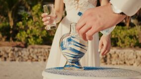 Newlyweds, groom and bride, on a beautiful tropical beach near the ocean. They add white and blue sand to the flask. Festive ceremony with sand. Art of a young stock video