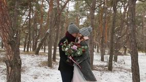 Newlyweds groom and bride hug kiss and warm each other in snowy pine forest during snowfall in slow motion. . Young stock footage