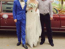 Newlyweds and Groomsman. Newlyweds with groomsman at red old car royalty free stock images