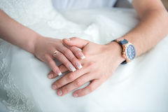 Newlyweds hands on a background of dress. Hands newlyweds with a bouquetA newly weding couple place their hands on a wedding bouquet Stock Photo