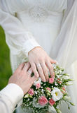 Newlyweds hands and a bouquet of flowers Royalty Free Stock Photos